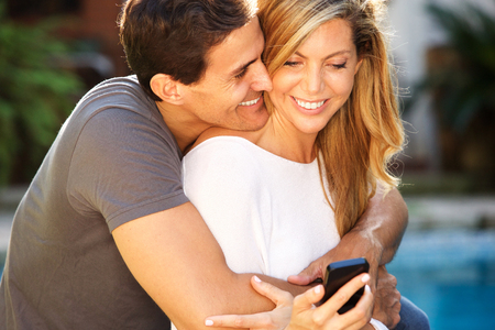 Close up portrait of smiling couple sitting outside in embrace looking at smart phone Standard-Bild