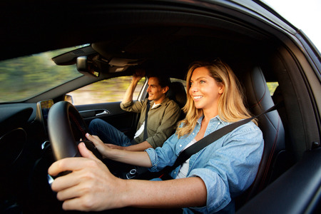 Close up portrait from side of happy couple smiling in car on road trip Standard-Bild