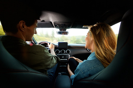 Portrait of couple from behind sitting in car together on road trip