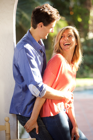 Portrait of laughing couple standing outside in close embrace