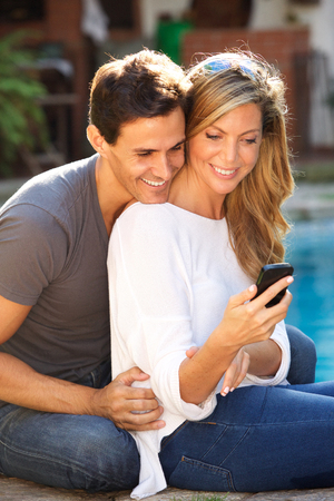 Portrait of happy couple sitting by pool looking at smart phone