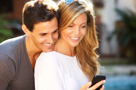 Close up portrait of smiling couple sitting outside looking at smart phone