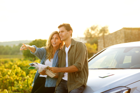 Portrait of couple sitting on car with map and woman pointing Standard-Bild
