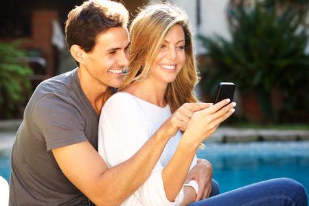 Close up portrait of happy couple sitting outside by pool taking selfie Standard-Bild