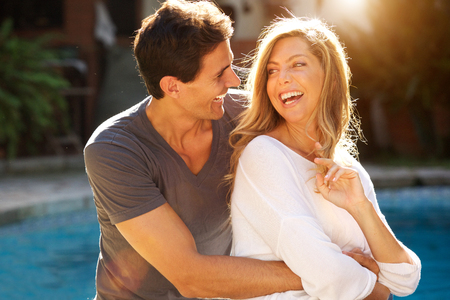 Close up portrait of laughing couple sitting together in embrace by pool Standard-Bild