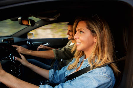 Close up portrait from side of beautiful pair laughing in car on road trip Standard-Bild