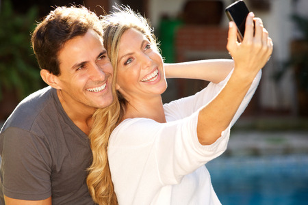 Close up portrait of couple sitting together by pool taking selfie
