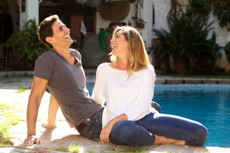 Portrait of laughing couple sitting together outside by pool