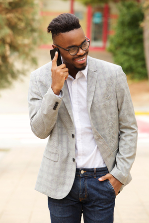 Portrait of young black businessman with glasses walking outside and talking on mobile phone Standard-Bild