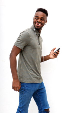 Side portrait of smiling young man walking with mobile phone and earphones against white background