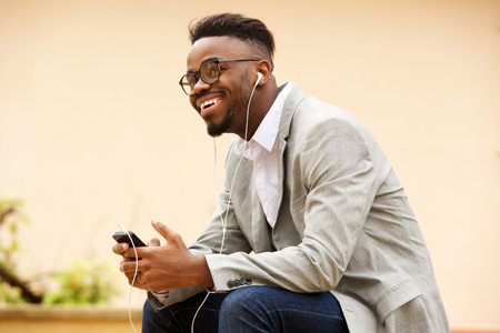 Side portrait of happy young black man sitting outside listening to music with earphones Standard-Bild