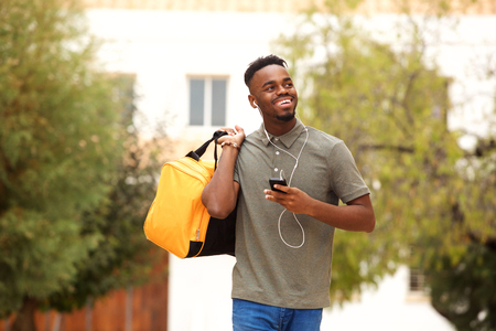 Portrait of happy young man listening to music and walking with bag Standard-Bild