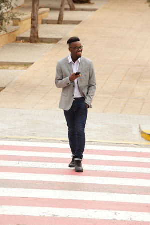 Full length portrait of cool young black businessman walking in city with cellphone Standard-Bild