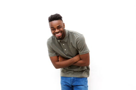 Portrait of young black man laughing with arms crossed against white background