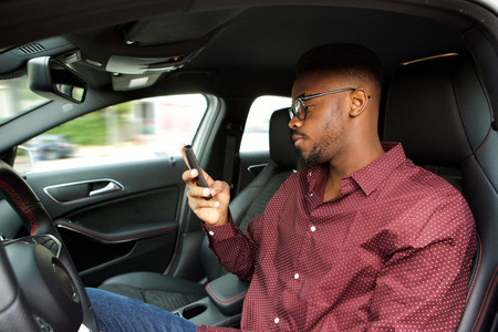Portrait of young african american man looking at cellphone before driving in car Standard-Bild