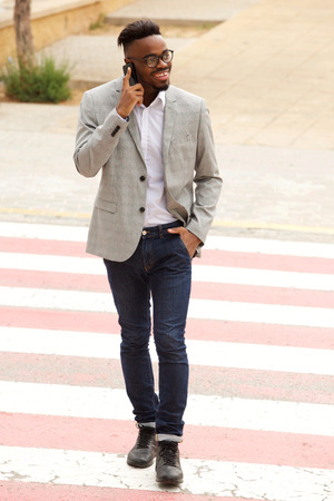 Portrait of cool young businessman walking and talking in the the city with cellphone  Standard-Bild