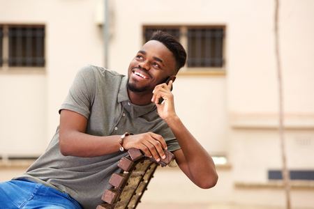 Portrait of young black man smiling and talking on mobile phone outside