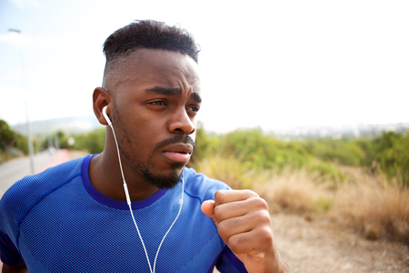 Close up portrait of fit young man running with earphones