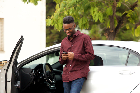 Portrait of happy young man standing by his car with cellphone