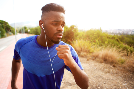 Close up portrait of fit young black man running with earphones