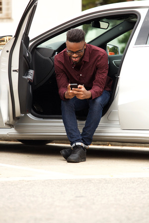 Portrait of african american man sitting in car sending text message 스톡 콘텐츠