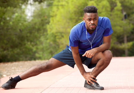 Portrait of fit young african american man doing stretching exercise while listening to music with earphones Standard-Bild
