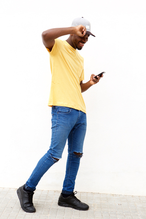 Full length portrait of cool young black with cellphone against white wall