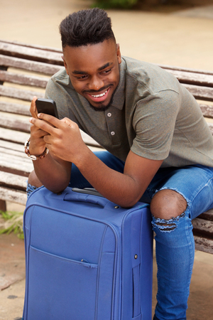 Portrait of young african american man sitting with mobile phone and suitcase