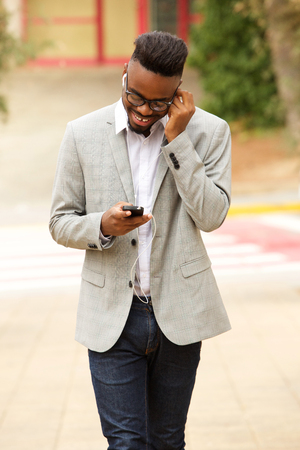 Portrait of young black man walking outside and listening to music with earphones