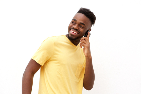 Portrait of young black man smiling and talking on mobile phone against white background