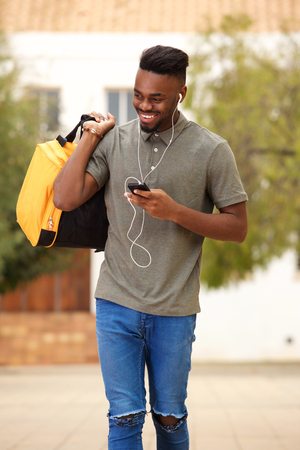 Portrait of a cool young guy walking with mobile phone and listening to music with earphones