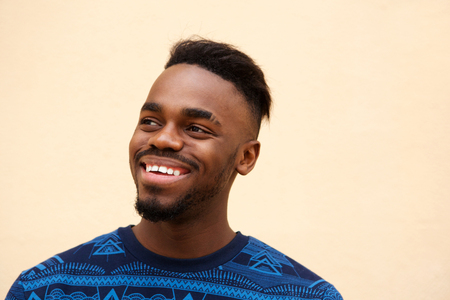 Close up portrait of young african american man smiling against blank wall
