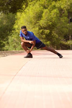 Full length portrait of sporty black man doing exercise stretches outside Standard-Bild