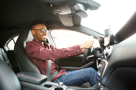 Side portrait of happy young black guy driving car Standard-Bild
