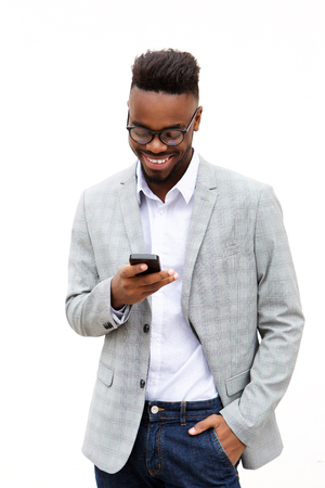 Portrait of smiling young businessman looking at mobile phone Standard-Bild