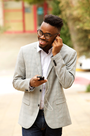 Portrait of happy young african american businessman with glasses walking with mobile phone and earphones
