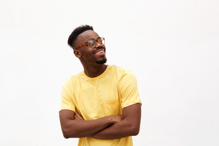 Portrait of a handsome young black man smiling with glasses against white background