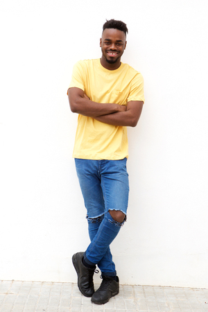 Full length portrait of smiling young black man leaning against white wall Standard-Bild