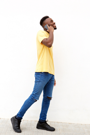 Full length portrait of young black man talking on cellphone against white wall