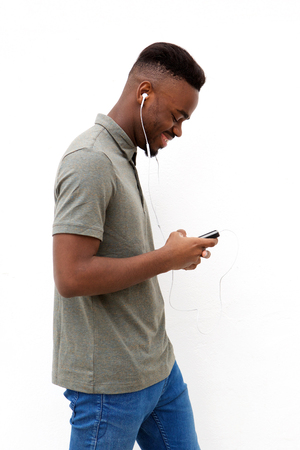 Side portrait of happy young black man walking with mobile and earphones against white wall Standard-Bild