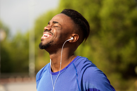 Portrait of happy young black man laughing with earphones in park