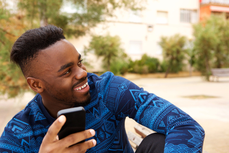 Portrait of cool black guy sitting outside with mobile phone