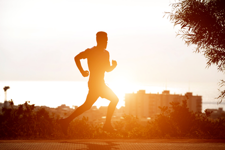 Silhouette of young black man running in sunset
