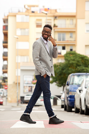 Full length side portrait of young african businessman walking and talking on cell phone in the city