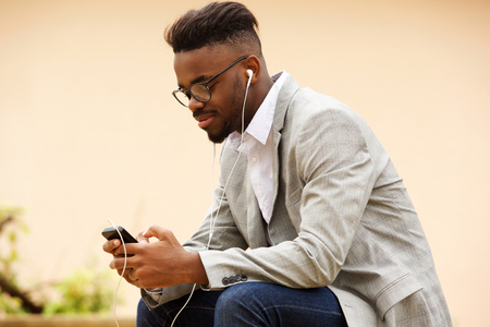 Side portrait of young guy sitting outside listening to music with mobile phone