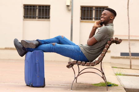 Side portrait of happy african american man sitting outside with suitcase and talking on cell phone