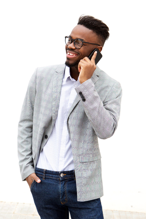 Portrait of young businessman talking on cell phone abasing white wall Standard-Bild