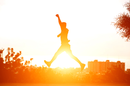 Young man running and jumping with sunset in background