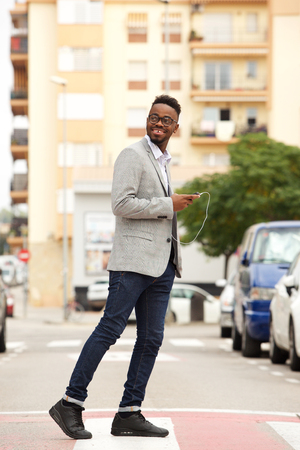 Full length side portrait of young black businessman walking in the city with mobile phone and earphones