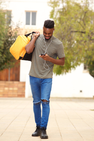 Full length portrait of young man walking with bag and listening to music with earphones  Standard-Bild